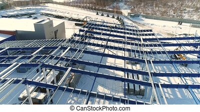 Construction of a modern factory or plant, Industrial area in winter, panoramic view from the air. Modern plant on the snow-covered field, the structural steel structure of a new commercial building
