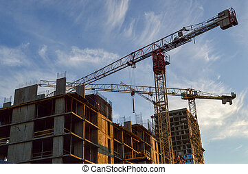 construction of a new residential concrete house. cranes are folding the new floor. metal rusty pins protrude from concrete blocks. the house has openings for windows