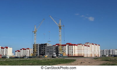 Construction of a residential house, a tower crane lifts the slab