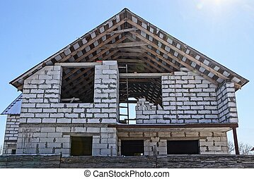 construction of a white brick house against the sky