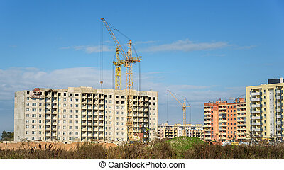construction of apartment buildings and crane on blue sky background