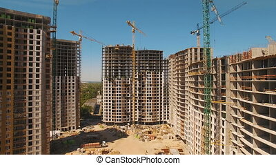 Construction of houses. Drone fly over construction site with tower cranes