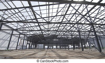 Construction of modern factory or warehouse, modern industrial exterior, panoramic view. Modern storehouse construction site, structural steel structure of new commercial building against.