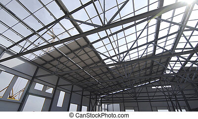 Construction of modern factory or warehouse, modern industrial exterior, panoramic view. Modern storehouse construction site, structural steel structure of new commercial building