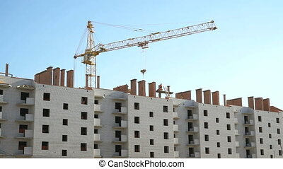 Construction crane working on the background construction of multi-storey brick building outdoors