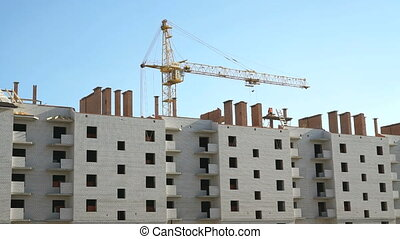Construction crane working on the background multi-family high-rise building outdoors