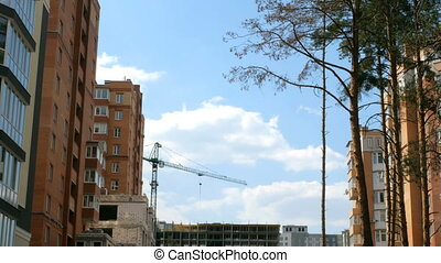 Construction of new homes in a residential area against the blue sky and clouds.