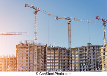Construction of residential real estate of their solid concrete and bricks. View of high-rise houses and cranes