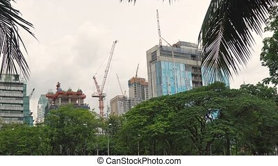 Construction of skyscrapers in a busy business district. Construction cranes are working on the building site, urbanization concept