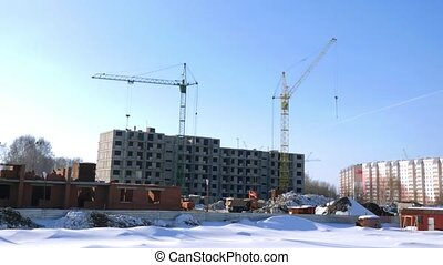 Construction of the building. Cranes working in the winter