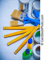 Construction paint tools with duct tapes and wooden meter on...