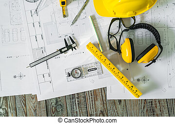 Construction plans with helmet and drawing tools on...