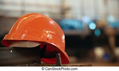 Construction plant. A helmet on a foreground. Mid shot
