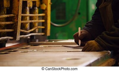 Construction plant. A worker making marks with a white...