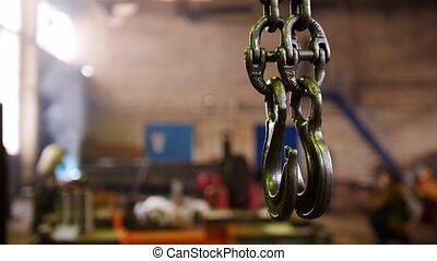 Construction plant. An industrial lifting chain with a hook...