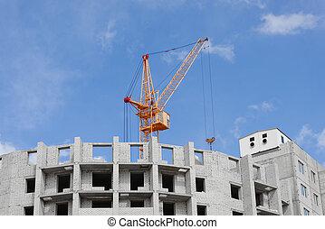 Construction project, construction site. Building, erection. Construction cranes. Cloudy turquoise sky.