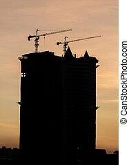 Construction project silhouette against sunset sky