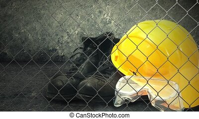 Construction helmet and industry safety equipment. Yellow hardhat, black boots and plastic protective goggles.