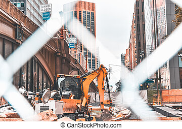 Construction scene in New York City. Excavator and several tools of construction. Edited with orange and teal colors.