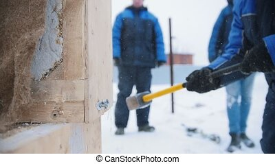 Construction site. A man hitting a wooden box with a hammer....