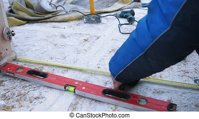 Construction site. A man measures the size of a structure using a tape measure and construction level