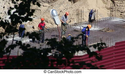 Construction site area with working builders unfocused