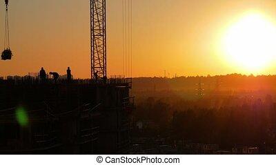 Construction site at sunset against the sun. Crane lifts concrete