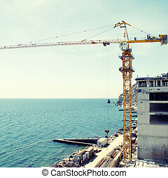 Construction site at the sea coast - Tall yellow crane on...