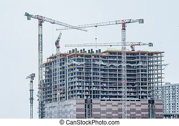 Construction site background. Hoisting cranes and new multi-storey buildings. Industrial background. modern urban building under construction with a crane. Industrial modern residential quarter of the city