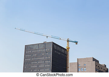 Construction site background. Hoisting cranes and new multi-storey buildings.