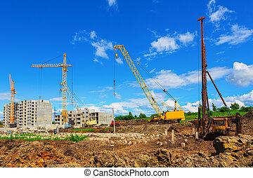 Cranes on the construction site beneath blue cloudy sky