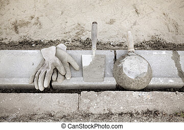Construction site, curb stone and mason tools