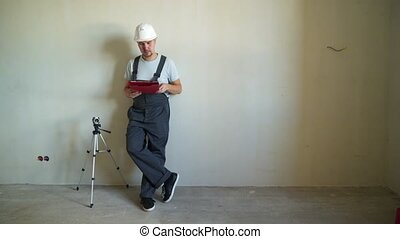 Construction Site Engineerer Working with Blueprint