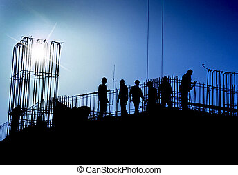 construction site with workers in silhouette back lit by sun