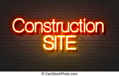 Construction site neon sign on brick wall background.