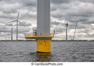 Construction site offshore windfarm near Dutch coast with cloudy sky