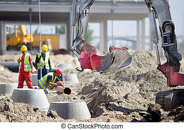 Construction site - Small excavator and workers at...
