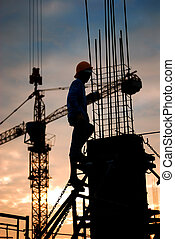 construction site - silhouette of constructionworker on ...