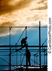 Construction site, silhouettes of workers against the light/