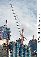 construction site - cranes and scaffoldings in a...