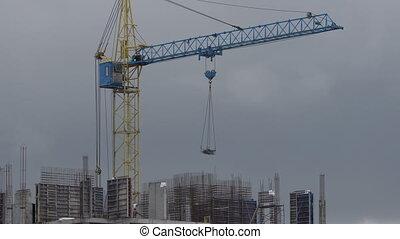 Construction site. Crane lifts cargo to floor.