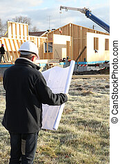 construction site supervisor looking at a blueprint