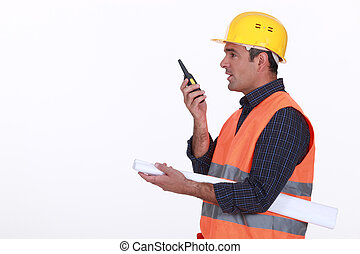 construction site supervisor talking on his walkie talkie