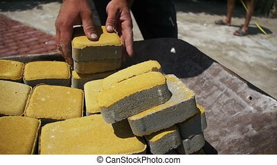 Construction Site, the Construction Worker Unloads the Stone Paving from the wheelbarrow. Slow Motion