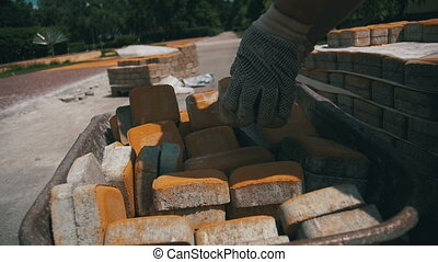 Construction Site, the Construction Worker Unloads the Stone...