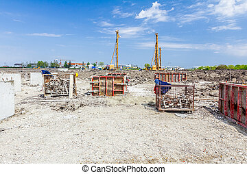 Construction site with big equipment for making concrete base, demountable molds