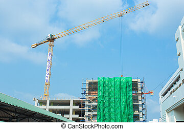 Construction site with cranes and blue sky background