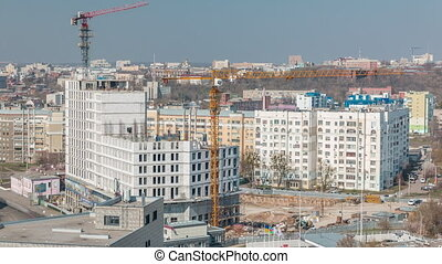 Construction site with lots of yellow cranes next to the ...