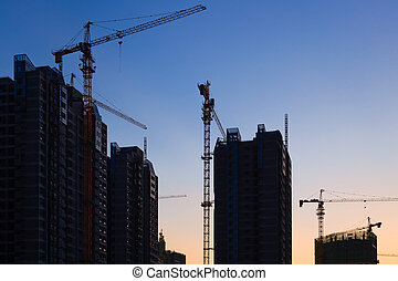 Construction site with many cranes at sunset