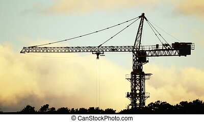 Construction site with tower crane at sunset